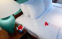 A pillow and flower on a bed