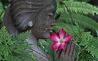A statue of a woman holds a flower in her hands